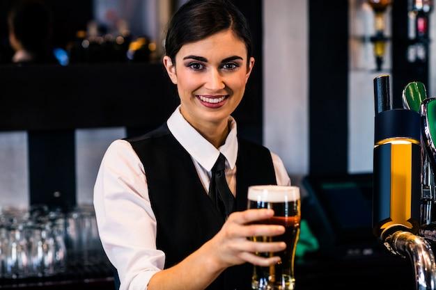 Garçonete servindo uma cerveja em um bar