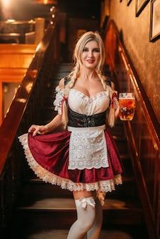 Garçonete sexy com caneca de cerveja fresca na escada em pub vintage.
