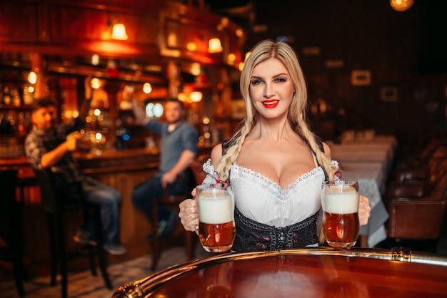 Garçonete sexy com seios grandes segura duas canecas de cerveja fresca no bar.