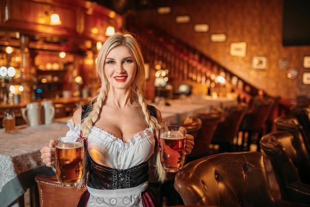Garçonete sexy segurando duas canecas de cerveja fresca no bar