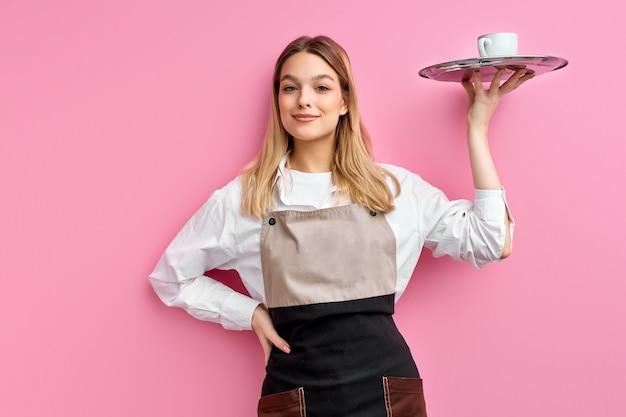 Garçonete simpática de avental, oferecendo uma xícara de café delicioso e saboroso na bandeja, sorrindo
