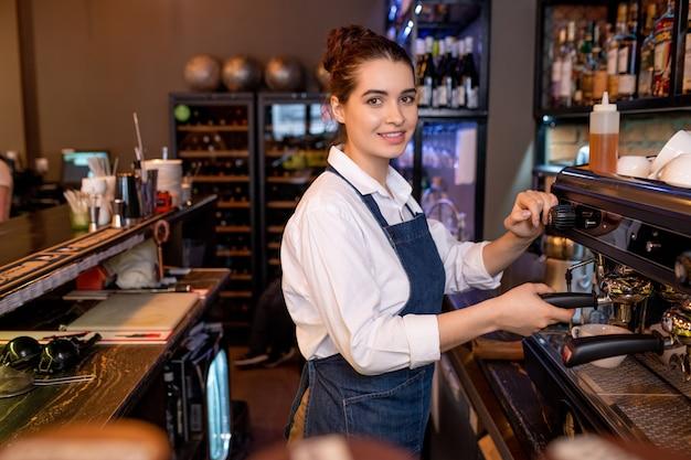 Garçonete simpática e bonita em trajes de trabalho preparando cappuccino enquanto está de pé ao lado da máquina de café no refeitório ou restaurante