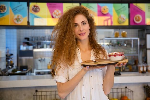 Garçonete sorridente segurando a bandeja com sobremesa no café