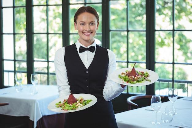 Garçonete sorridente segurando pratos