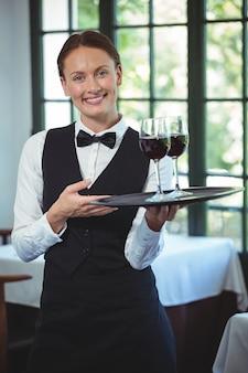 Garçonete sorridente segurando uma bandeja com copos de vinho tinto