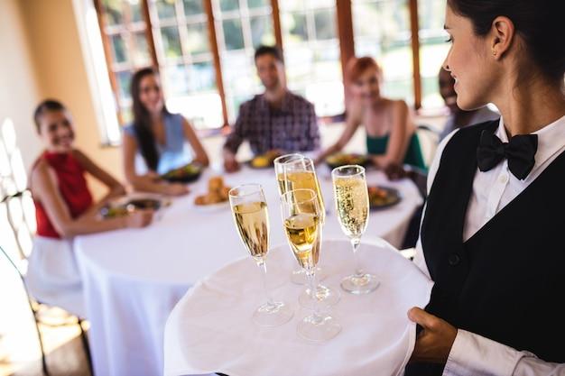 Garçonete, taças de champanhe na bandeja no restaurante