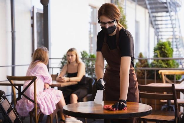 Garçonete trabalha em um restaurante com uma máscara médica, luvas durante uma pandemia de coronavírus