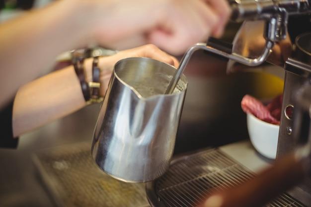 Garçonete usando a máquina de café