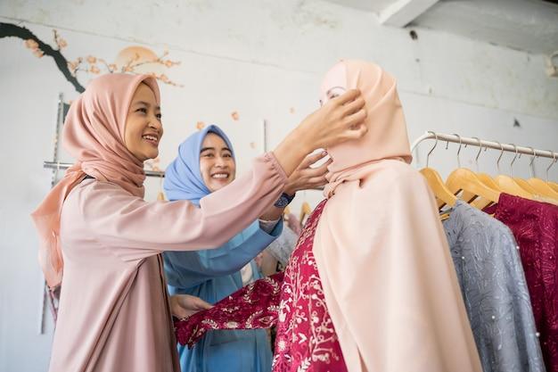 Garçonetes asiáticas com véu servindo mulheres comprando lenços na cabeça do manequim