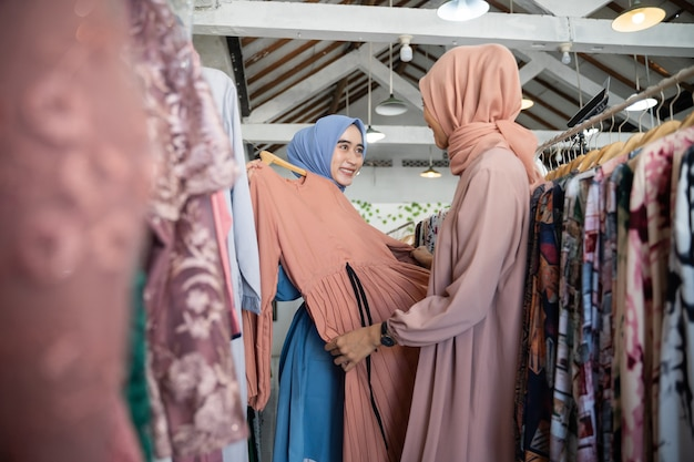 Garçonetes asiáticas com véu servindo mulheres que compram roupas em cabides