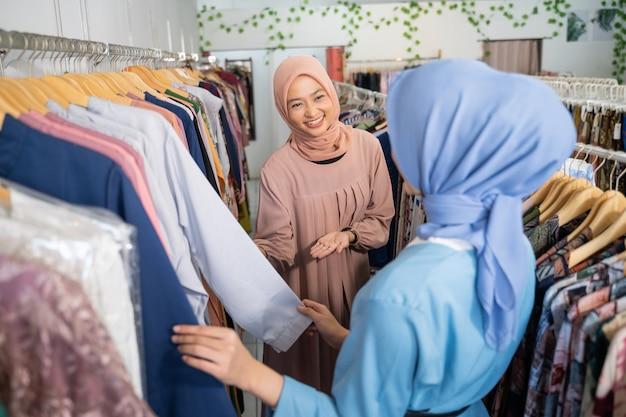 Garçonetes asiáticas com véu servindo mulheres que compram um robe