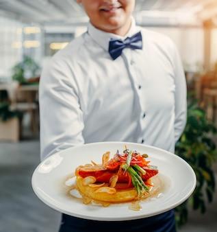 Garçons segurando o prato de salmão grelhado, purê de batata, coberto com caviar vermelho, aspargos