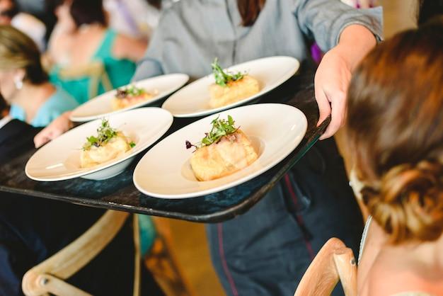 Garçons servindo pratos de aperitivos para jantares e convidados para uma festa.