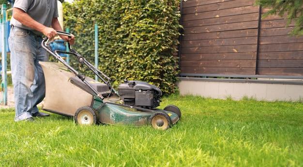Gardener corta a grama com um cortador de grama no quintal.