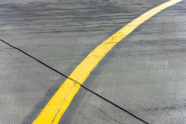 Garfo amarelo da faixa de direção perto de uma pista de aeródromo.