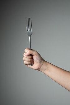 Garfo com a mão na cozinha de utensílio de fundo cinza para cozinhar