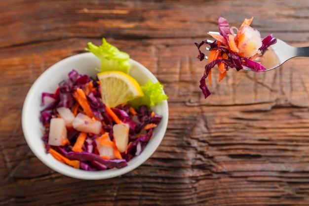 Garfo com comida em uma mão feminina sobre um prato de salada de repolho em uma superfície de madeira