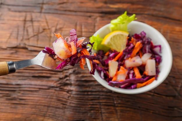 Garfo com comida em uma mão feminina sobre um prato de salada lenta de couve em um fundo de madeira. foto horizontal