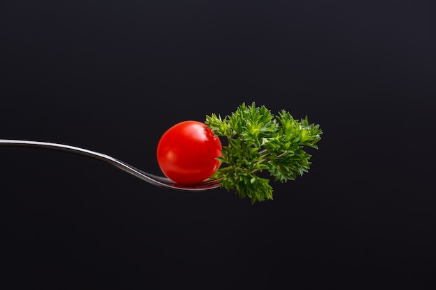 Garfo com tomate cereja e folha de salsa em isolado no preto