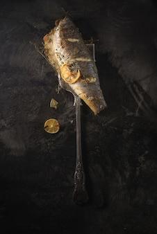 Garfo de aço inoxidável ao lado de peixe cru