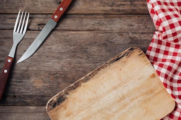 Garfo de bife e faca em fundo de madeira