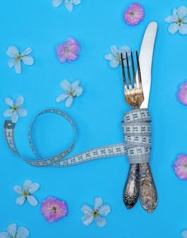 Garfo de ferro e faca envolto em uma fita métrica