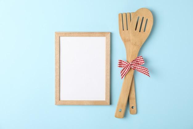 Garfo de madeira, espátula de cozinha e espaço em branco para texto em azul
