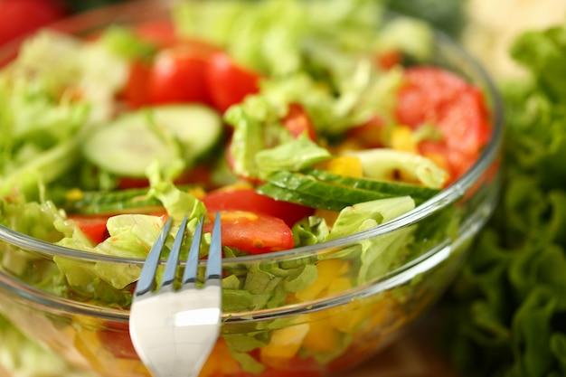 Garfo de prata no prato mistura salada de legumes frescos