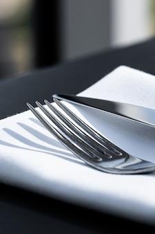 Garfo e faca com guardanapo branco na mesa em restaurante de luxo ao ar livre, menu de jantar fino para casamento ...