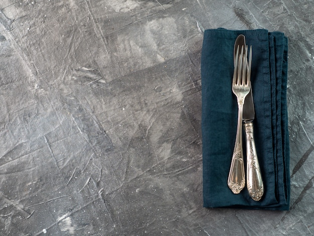 Garfo e faca de prata no guardanapo de linho verde esmeralda escuro sobre textura cinza