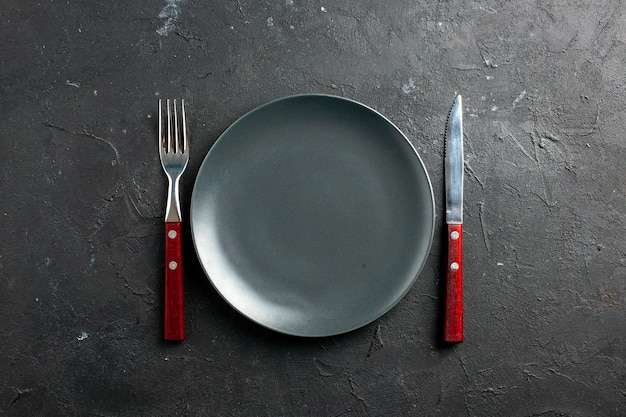 Garfo e faca de prato de salada preta de vista superior na superfície preta