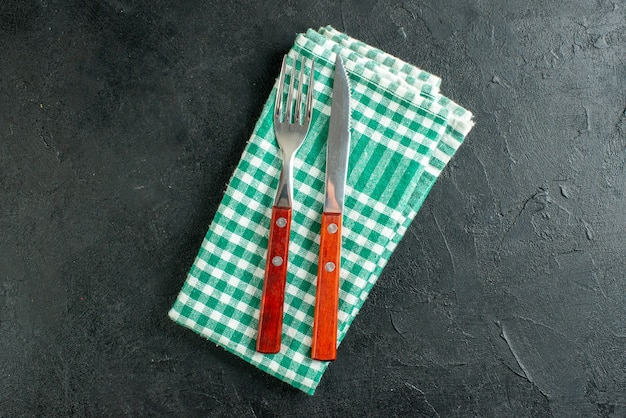 Garfo e faca de prato redondo de vista superior em guardanapo xadrez verde e branco em superfície preta