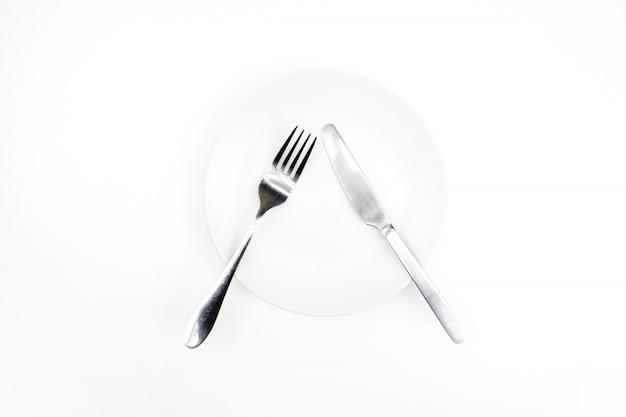 Garfo e faca em um prato vazio em um branco