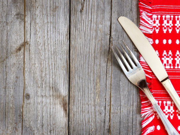 Garfo e faca na toalha de cozinha em uma vista de mesa de madeira com espaço de cópia