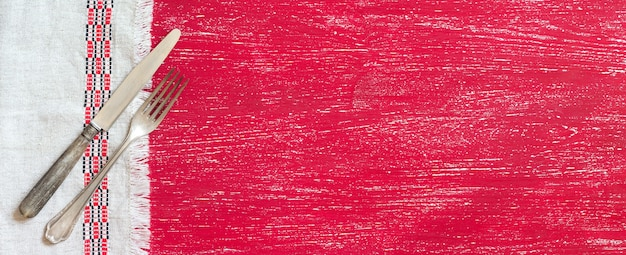 Garfo e faca vintage em guardanapo em madeira vermelha com espaço de cópia