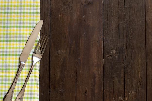Garfo e faca vintage em um guardanapo colorido na mesa de madeira
