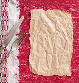 Garfo e faca vintage no guardanapo na mesa de madeira vermelha com papel artesanal