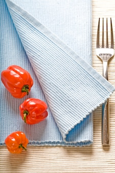 Garfo e pimentos no guardanapo azul