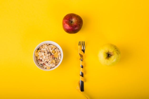 Garfo em fita métrica entre maçãs e tigela de flocos