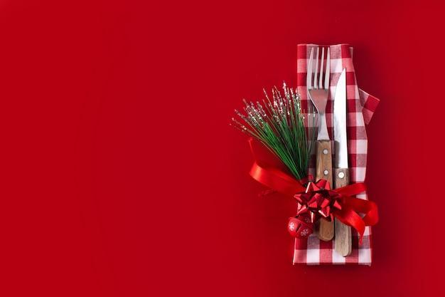 Garfo, faca e decoração de natal na superfície vermelha. conceito de jantar de natal. Foto Premium