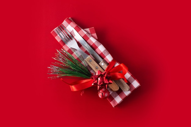 Garfo, faca e decoração de natal na superfície vermelha. conceito de jantar de natal.