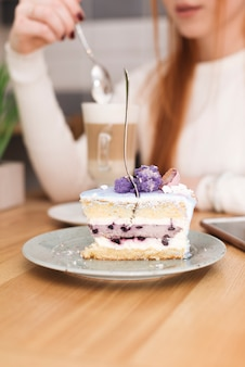 Garfo inserido no pedaço de bolo delicioso em camadas na frente da mulher com latte macchiato