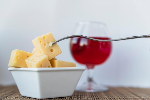Garfo perto conjunto de queijo fresco em pires e copo de bebida