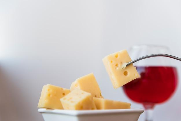 Garfo perto conjunto de queijo fresco em pires e copo de vinho