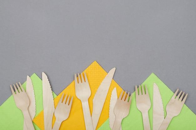 Garfos de madeira e facas em guardanapos laranja e verdes em fundo cinza, vista superior. talheres descartáveis ecológicos de material natural.