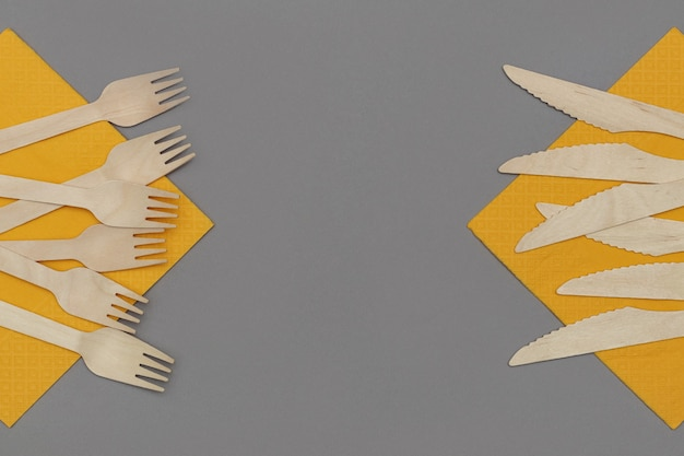Garfos de madeira e facas em guardanapos laranja em fundo cinza, vista superior. talheres descartáveis ecológicos de material natural.