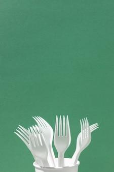 Garfos de plástico branco em um espaço de cópia de xícara