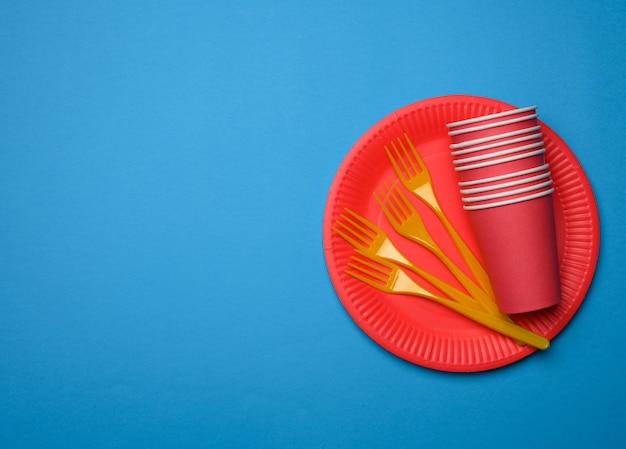 Garfos de plástico laranja e pratos descartáveis de papel vermelho vazios em um fundo azul, vista superior, conjunto