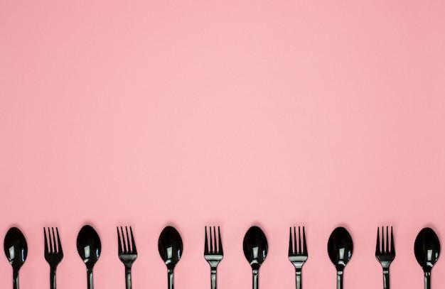 Garfos e colheres em um fundo rosa. conceito mínimo. sem plástico.