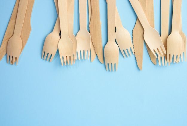 Garfos e facas de madeira em um fundo azul, desperdício zero, espaço de cópia